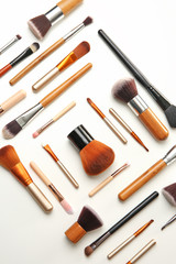 Flat lay composition with makeup brushes of professional artist on white background
