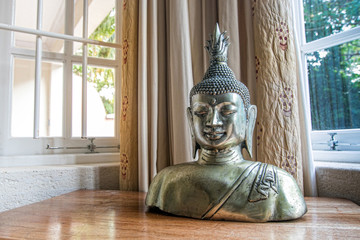 Decorative bust of Buddha the God in a room.