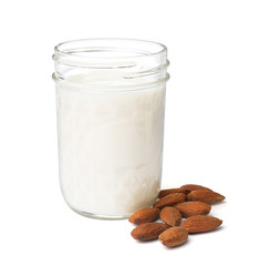 Jar with almond milk and nuts on white background