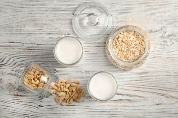 Composition with peanut and oat milk on wooden background