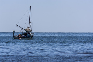 fishermen on a wooden boat hunt fish in the sea with rods and nets.beautiful blue and crystal clear water in the summer season. fishing in the ocean.