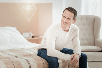 Waiting for you. Joyful pleasant stylish man sitting in the bedroom smiling and looking aside.