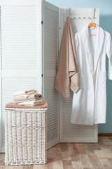 Bathroom interior with laundry basket and soft towels