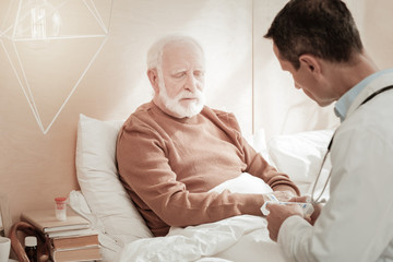 I need help. Sad frustrated gray-haired man siting on the bed near a doctor having bad mood and closing his eyes.