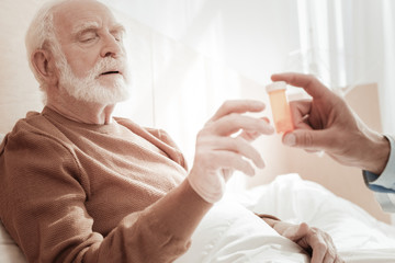 I need this. Sick exhausted aged man lying on the bed lifting his hand and taking pills.