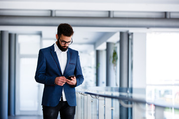Young Businessman Using Mobile Phone At Workplace