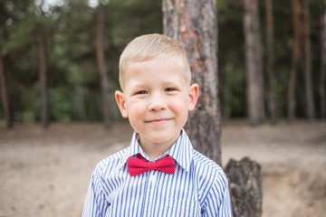 Portrait of cute funny little caucasian boy outdoors. Positive smiling blonde boy wearing blue shirt and red bow tie looks at camera. Horizontal color photography.