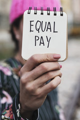 woman with a pink hat and the text equal pay.