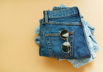 Picture of jeans with glasses on craft wooden background