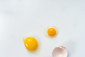 Yolk of broken egg in eggshell decorated with pink sisal nest on the minimalist white background