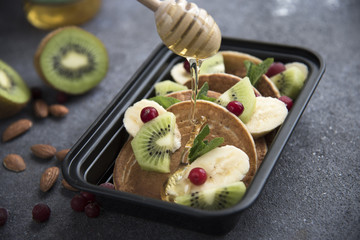 container with pancakes, berries, fruits and honey. food delivery. healthy eating