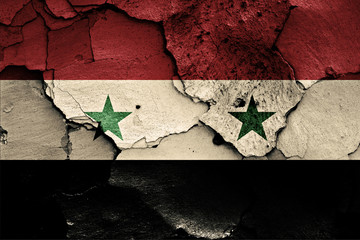 flag of Syria painted on cracked wall
