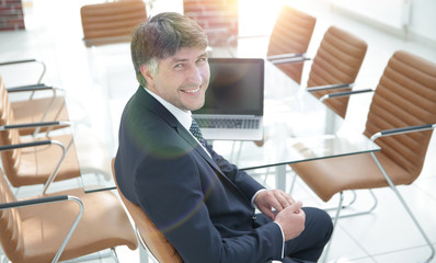 smiling manager sitting at work desk in meeting room.