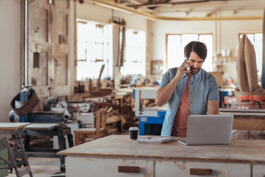 Woodworker using a phone and laptop in his large workshop