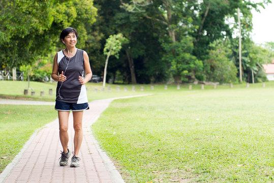 Front view of senior Asian woman jogging through park