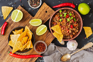 Chili con carne.Mexican chili food with meat and corn chips nachos on a rustic background. View from above.