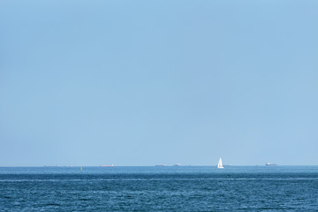 A small sailing ship alone in the sea against a blue sky background
