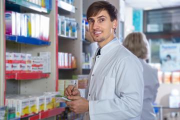 Male pharmacist posing in drugstore