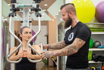 Bearded coach helps a woman in a gym.