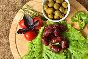 Hunting sausages on a wooden board with lettuce, basil, cherry tomatoes, paprika and olives.