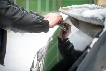 Removing snow from your car with a brush