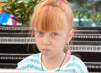 Portrait of a beautiful redheaded little girl. Child sad