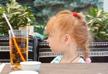 Beautiful red-haired little girl in a cafe.