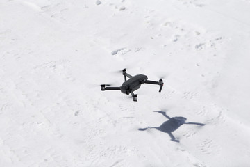 Drone Hovering over the snow taking pictures of white winter nature in the mountains