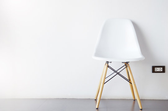 single modern white chair furniture with wood legs with wall in room background