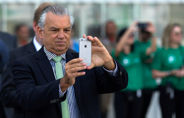 The CEO of Brazilian planemaker Embraer SA, Souza e Silva, takes a picture during a ceremony as Embraer delivers first E2-190 jet to Norway's Wideroe at the company's headquarters in Sao Jose dos Campos