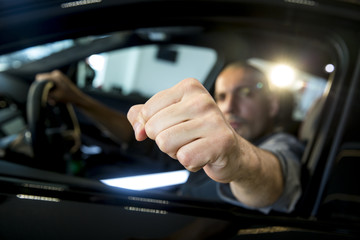 A man in the car vith fists clenched, focused on the fist