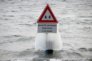 frozen water as ice, created by wind and waves at Zevenhuizerplas in Oud Verlaat, the Netherlands on warning sign for deep swimmingwater