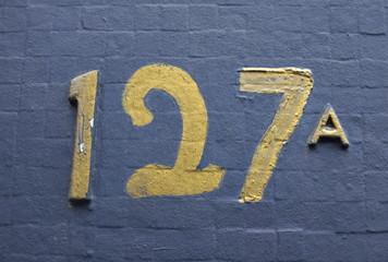 127 a. Cent vingt sept a. Chiffres dorés sur mur bleu