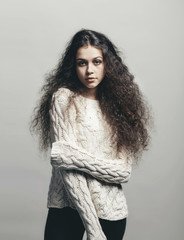 Portrait of confident woman with curly hair standing against gray background