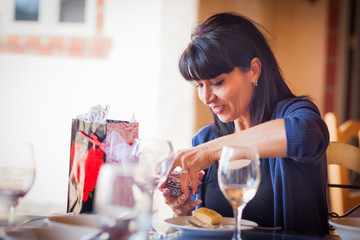 Pretty Italian Woman Enjoys Opening Gift From Friends on Patio Restaurant