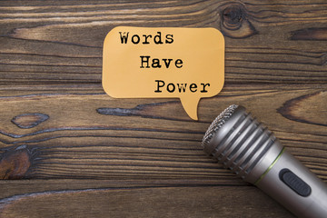 words have power and microphone, on wood texture background.