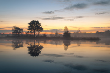 Beautiful misty morning with nice colors in the sky and great refelctions on the lake. Taken at...