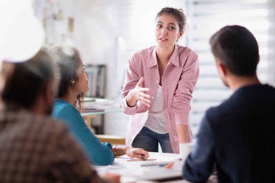 meeting at the company. A young woman leads a multi-ethnic group