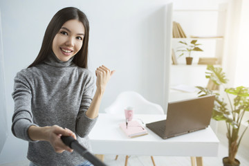 Live stream of girl showing her table in the corner of the room to her followers. Also there are a cup and a notebook there and laptop as well. She is happy and proud to show it to the whole world.