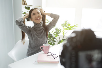 Funny and happy blogger is making a new video. She has split her hair into two ponytails and laughing out loud. She is enjoying the process of vlogging because it is her hobby.