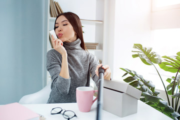 Cool selfie of a girl that holds a small tube of and cream close to her face and showing that she is kissing it. This is a typical beauty blogger's selfie.