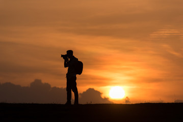 silhouette Photographer stand on the hill and mountains at sunset time