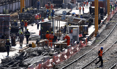 Employees work next to railroad tracks in Buenos Aires