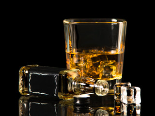 Whiskey glass with ice and small bottle on black isolated background.