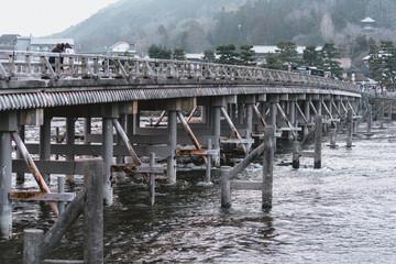 Kyoto, Japan - Jan 19 2018: Togetsu-kyo Bridge in Arashiyama, Kyoto, Japan. It is a 155-meter bridge over the Katsura River flowing leisurely in Saga Arashiyama, ancient capital of Kyoto.