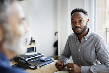 Confident businessman looking at male colleague in office