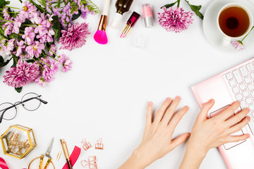 Flatlay arrangement with cup of tea, flowers, cosmetics, glasses, laptop and woman's hands printing on pink laptop, stylish business mockup, copyspace