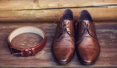 Brown leather shoes and belt on wooden floor