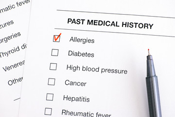 Past medical history questionary with ticked Allergies and pen.