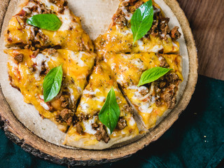 fresh baked crisp pizza with meat cheese and fresh Basil leaf